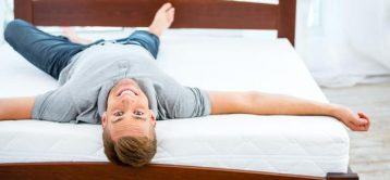 49654403 - photo of young man lying on nice white bed. young man demonstrating quality of mattress